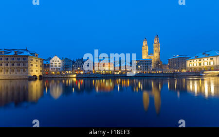 Zurich with the Grossmunster and the Limmat river at night - Stock Photo
