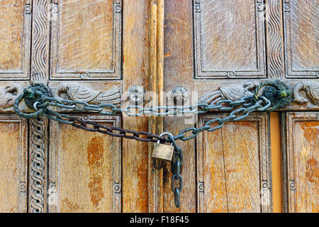 An old wooden door locked by a chain with a padlock - Stock Photo