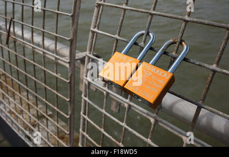 Padlocks fixed to the railings on the North Pier in Blackpool - Stock Photo