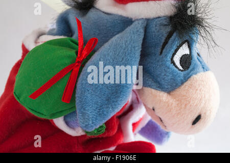 Xmas Santa Eeyore carrying sack of presents soft cuddly toy from Winnie the Pooh set on white background - Stock Photo