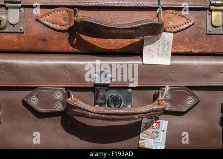 Close up view of two old leather suitcases on display for sale at an antiques store. - Stock Photo