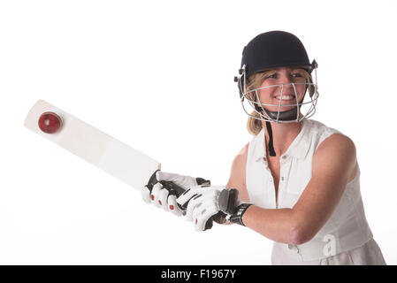 Female club cricket player hitting cricket ball with a bat cricket - Stock Photo