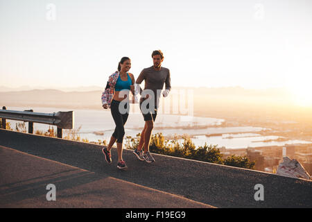 Young couple jogging early in morning. Young man and woman running outdoors on a hillside road. - Stock Photo