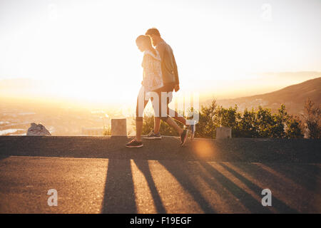 Couple walk along road at sunrise. Couple talking a walk on hillside road with bright sunlight. - Stock Photo