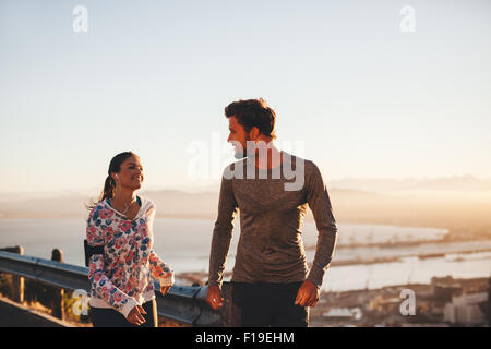 Image of fit young man and woman jogging on country road, looking at each other. Runners enjoying morning run. - Stock Photo