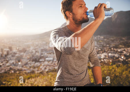 Young runner taking a break after morning run drinking water. Young man relaxing after a running training session - Stock Photo