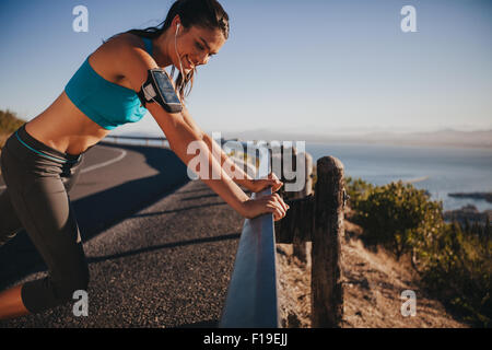 Young woman leaning on road guardrail smiling. Woman runner on country road taking a break after running exercise. - Stock Photo