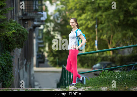Young sporty woman standing outdoors after a workout in summer day. Workout outdoors. - Stock Photo