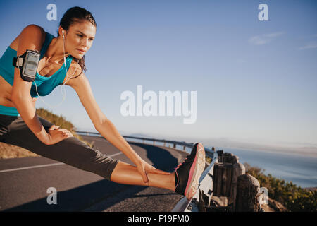 Outdoor shot of woman stretching her legs before a run. Determined runner preparing for outdoor training looking - Stock Photo