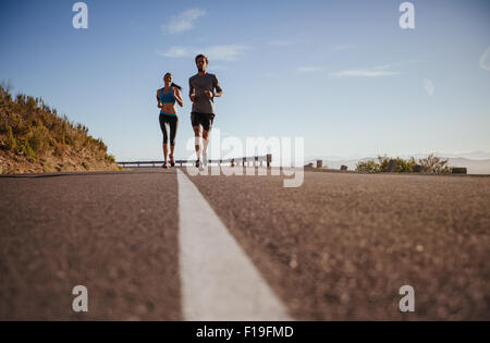 Two young people running on country road, low angle shot of runners on open road on  a summer day. - Stock Photo