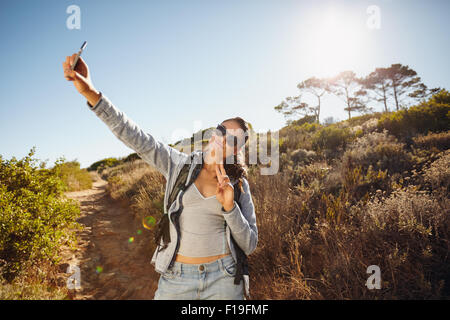 Happy and energetic young woman taking a selfie. She is holding the mobile phone camera high posing and gesturing - Stock Photo