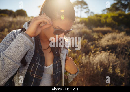 Close up shot of young woman hiking on a summer day. Caucasian female hiker wearing sunglasses looking down with - Stock Photo