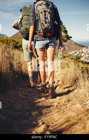 Rear view of young couple trekking together in countryside. Hiker couple walking through pathway on mountain. Hiking - Stock Photo