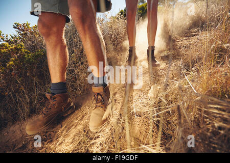 Low angle view of young people walking on mountain trail. Couple hiking on dirt path coming downhill. Cropped shot - Stock Photo