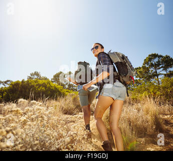 Young people doing a uphill climb while hiking in countryside. Woman with map looking back over her shoulder smiling - Stock Photo