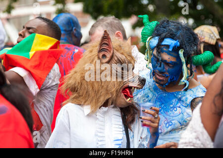 Londoners enjoy the Notting Hill Carnival, Europe's largest street festival with its many dancers, bands, sounds - Stock Photo