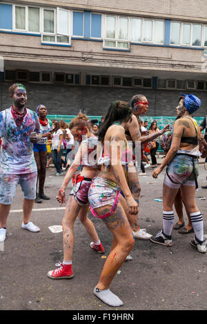 A group of carnival revellers dance in the street and enjoy the Notting Hill Carnival, Europe's largest street festival - Stock Photo