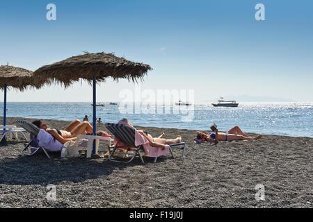 Three female sunbathers on Kamari beach, Santorini, Greece. - Stock Photo