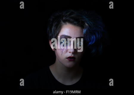 Teen girl in scary makeup on black background. - Stock Photo