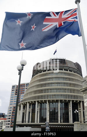 The New Zealand flag flies high over Parliament House at Wellington, New Zealand - Stock Photo