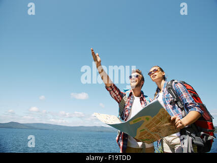Cheerful young man showing something to his girlfriend in the sky - Stock Photo