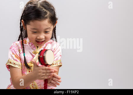 Little girl playing Chinese toy drum on white background. - Stock Photo