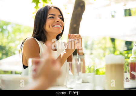 Happy woman sitting a tthe table in outdoors restaurant - Stock Photo