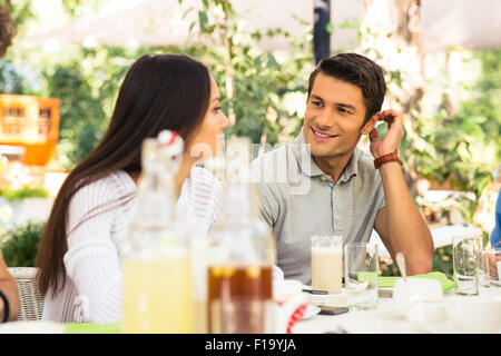 Portrait of a happy couple sitting in outdoor restaurant - Stock Photo