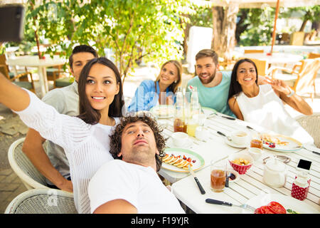 Portrait of a happy friends making selfie photo in outdoor restaurant - Stock Photo