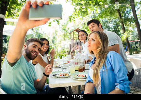 Portrait of a friends making selfie photo on smartphone in outdoor restaurant - Stock Photo