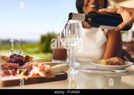 Hands of a man pouring white wine in two glasses from bottle with a woman smiling in background at winery. Focus - Stock Photo