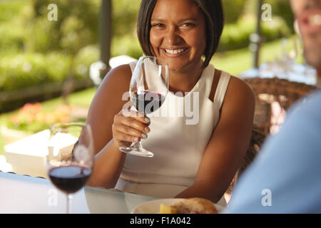 Portrait of beautiful young woman sitting at a table in winery holding a glass of red wine and smiling at camera.