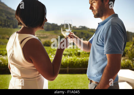 Closeup shot of young couple toasting wine while standing outdoors at winery restaurant with vineyard in background. - Stock Photo