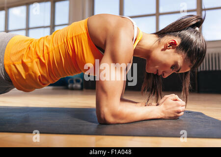 Side view of attractive young woman doing core exercise on fitness mat in the gym. Female doing press-ups in health - Stock Photo