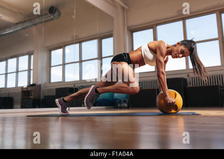 Portrait of a fit and muscular woman doing intense core workout with kettlebell in gym. Female exercising at crossfit - Stock Photo