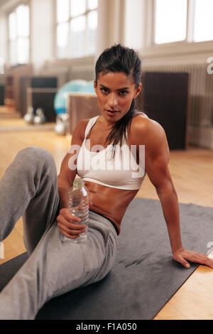 Young woman sitting on fitness mat holding water bottle. Fitness female relaxing after exercise. - Stock Photo