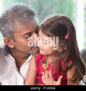 Happy Indian family at home. Asian dad kissing his toddler. Father and daughter indoor lifestyle. - Stock Photo