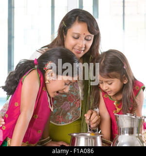 Asian family cooking food together in kitchen. Indian mother and children preparing meal at home. Traditional India - Stock Photo