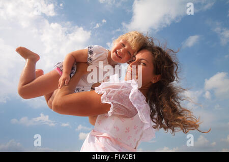 family, child and happiness concept - mother throws up her daughter - Stock Photo