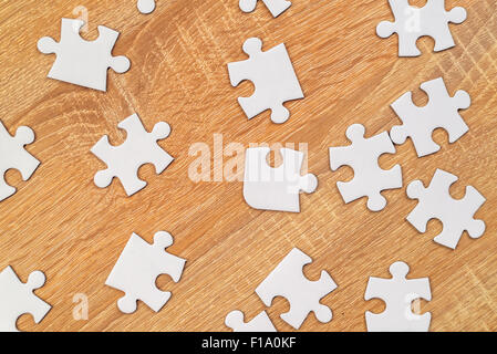 Blank white jigsaw puzzle pieces scattered on wooden table, top view - Stock Photo