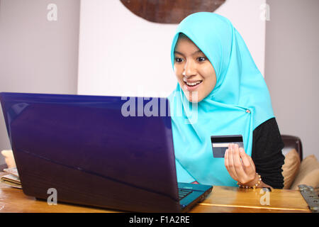 portrait of young muslim woman working on laptop and make a payment using credit card - Stock Photo