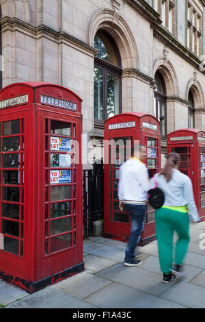 People passing K6 Old type GPO, or BT red Telephone Boxes advertised as being  'To Let' with various uses being - Stock Photo