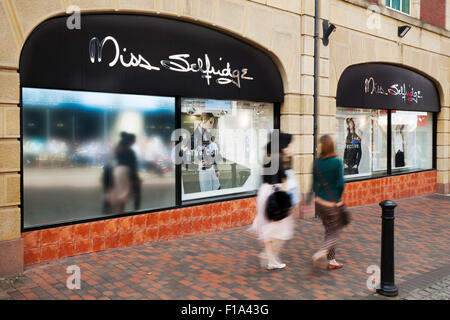 Sale promotion as Shoppers pass Miss Selfridge retail outlet in Preston, Lancashire, UK - Stock Photo