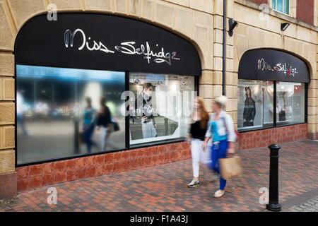 Sale promotion as Shoppers pass Miss Selfridge retail outlet in Preston, Lancashire, UK - Stock Photo
