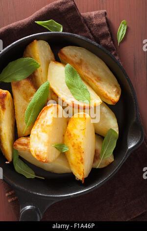 baked potato wedges in black frying pan - Stock Photo