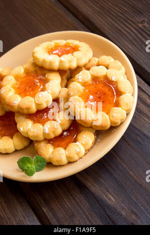 Fresh cookies with fruit jelly on plate over rustic wooden background - Stock Photo