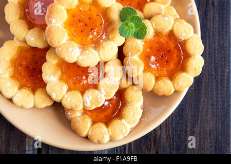 Fresh cookies with fruit jelly over rustic wooden background close up - Stock Photo