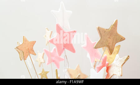 Details of a cake decoration, closeup view on stars of sugar in white, pink and gold colors. - Stock Photo