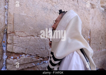 Ultra Orthodox Jew wrapped with traditional religious Talit shawl and Tefillin phylacteries at prayer in the Western - Stock Photo