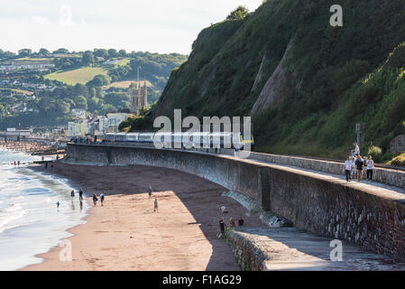 Teignmouth, Devon. 2015. A diesel passenger train en route along the famous Brunel seawall coast rail. Town in the - Stock Photo